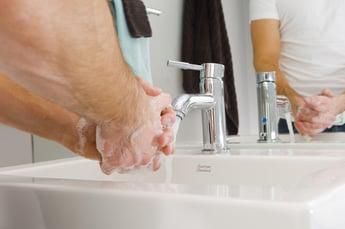 Guy washing hands in sink.